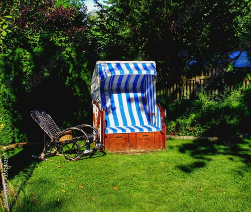 Fotografering Hooded Beach Chair And Deck Chair On Grassy Field