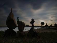 Balancing Rocks At Riverbank Against Sky