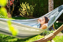 Young Girl Relaxing Having Nap In Hammock In Garden At Home At Bright Sunny Day. Slow Living, Gadget Detox And Weekend Leisure Activity. Quarantine And Self Isolation Period