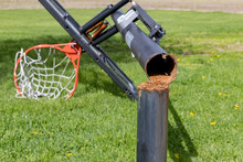 Outdoor Basketball Hoop With In-ground Pole Rusty And Broken From Dunking And Wind Damage