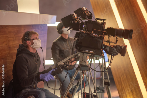 Fotografiet masked cameraman is filming a television show in the studio
