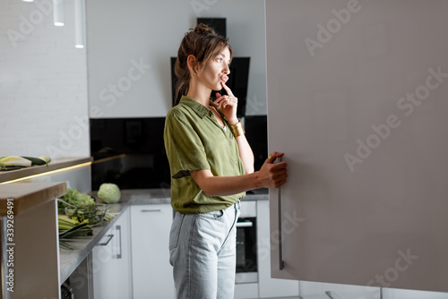 Fotografiet Young woman looking into the fridge, feeling hungry at night