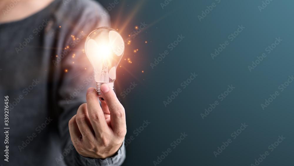 Fototapeta Hand of man holding illuminated light bulb, idea, innovation and inspiration concept.concept creativity with bulbs that shine glitter.