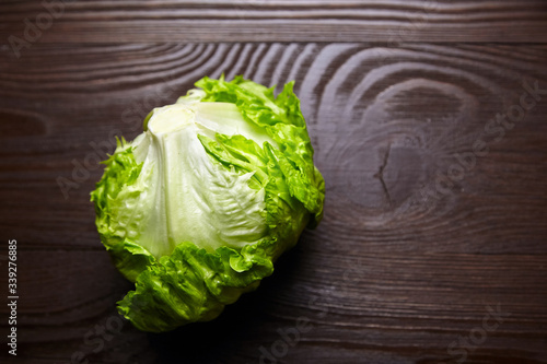 Fototapeta Iceberg lettuce on wooden table background, top view obraz