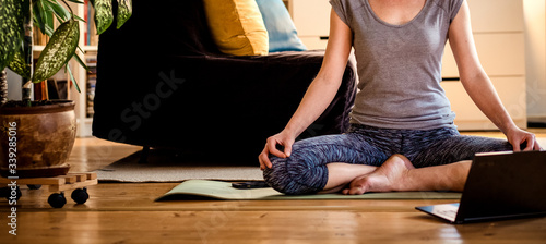Fototapeta woman doing yoga workout at home watching videos online on laptop computer obraz