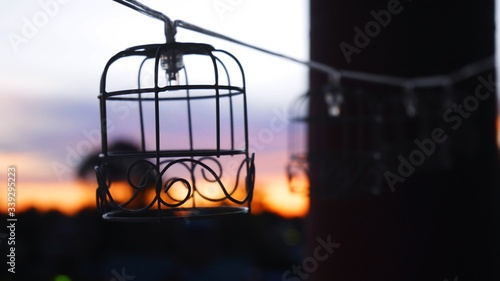 Tablou Canvas Christmas Lights In Birdcages Against Sky During Sunset