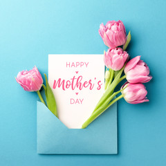 Bouquet of pink tulips in turquoise envelope on turquoise background. Happy Mother's Day greeting card. Flat lay, top view.