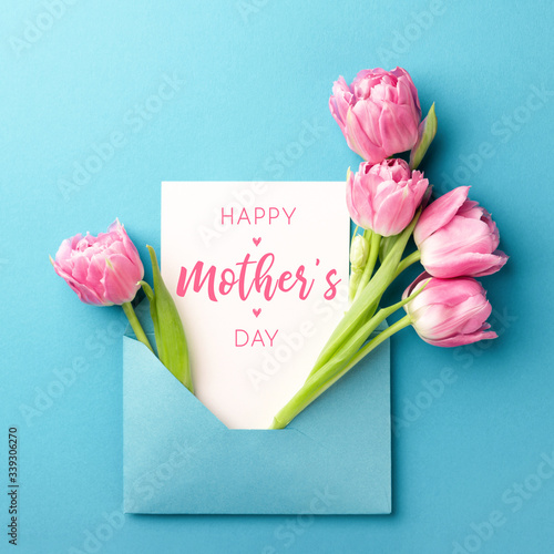 Bouquet of pink tulips in turquoise envelope on turquoise background. Happy Mother's Day greeting card. Flat lay, top view. Fototapete