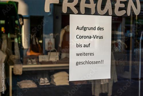 """Fototapeta Schaufenster von Ladengeschäft mit Schild """"Geschlossen wegen Corona-Virus"""", in Deutsch, mit Auslagen und die Spiegelung der Umgebung in Unschärfe zur Zeit der Corona Covid-19 Pandemie im März 2020 obraz"""