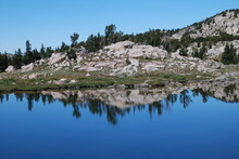 Lake With Reflection By Hill Against Clear Sky