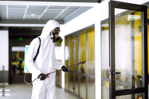 Obraz Disinfecting of office to prevent COVID-19, Man in protective hazmat suit with  with spray chemicals to preventing the spread of coronavirus, pandemic in quarantine city. Cleaning concept. - fototapety do salonu