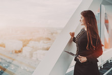 A Dainty Mature Hispanic Woman Entrepreneur With A Digital Tablet Is Standing Near The Window Of A Business Office Skyscraper And Looking At Highway; A Copy Space Place On The Left For An Advert Text