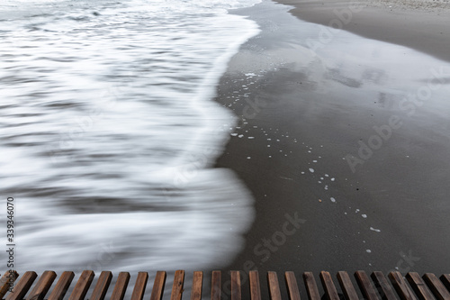 Photo Wave rolls ashore, long exposure black and white photography