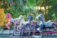 Rocking Horse On Gravel Against Trees In Playground