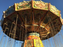 Low Angle View Of Chain Swing Carousel Against Sky