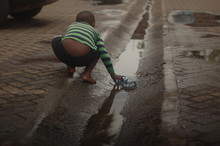 Rear View Of Boy By Puddle On ...