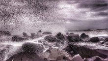 Wave Splashing On Rocky Shore Against Cloudy Sky