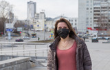 Woman of European appearance in a black medical mask on her face from the coronavirus looks at the background of empty Grod and stre