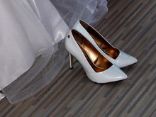 High Angle View Of White Stilettos By Wedding Dress On Hardwood Floor