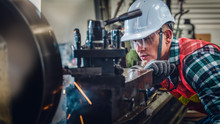 Industrial Background Of Caucasian Mechanics Engineer Operating Lathe Machine For Metalwork In Metal Work Factory