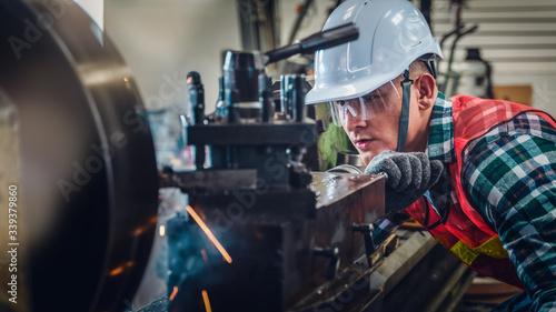 Cuadros en Lienzo industrial background of caucasian mechanics engineer operating lathe machine fo