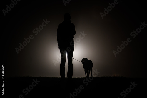 Foto Man Standing By Dog On Field At Night