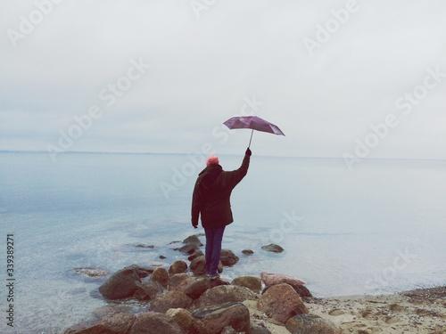 Fényképezés Rear View Of Man Holding Aloft Umbrella While Standing On Rocks At Beach Against