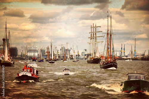 Foto Boats And Ships Sailing On Sea Against Cloudy Sky