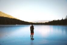 Man Standing At Shore Of Trillium Lake Against Sky