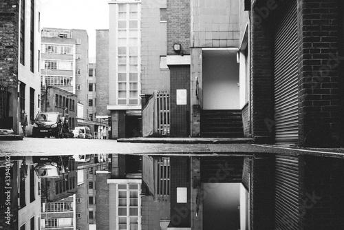 Canvas Print Cars And Buildings Reflecting In Puddle On Street