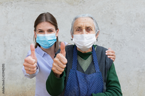Obraz Caregiver with elderly ill woman showing thumbs up - fototapety do salonu