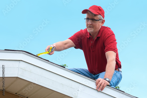 Fototapeta Wind mitigation inspector wearing safety goggles doing inspection on new roof to create a report and risk rating for homeowner to send to their insurance company to receive deductions in policy costs