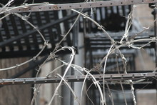 Close-up Of Barbed Wire Fence Against Building
