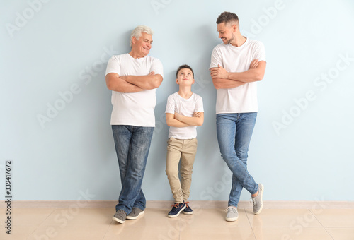 Leinwand Poster Man with his father and son near color wall