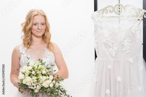 Photo Romantic young bride in elegant hotel room in white lace wedding dress with makeup and wavy blonde hair with wedding bouquet in her hands getting ready in bride's morning