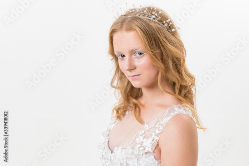 Photo Romantic young bride isolated on white in white lace wedding dress with makeup and wavy blonde hair with pearl jewelry getting ready in bride's morning