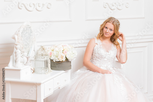 Photo Romantic young bride in hotel room at elegant table in white lace wedding dress with makeup and wavy blonde hair with wedding bouquet in her hands getting ready in bride's morning