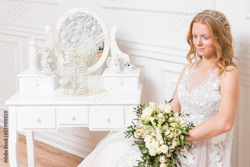 Romantic young bride in hotel room at elegant table in white lace wedding dress with makeup and wavy blonde hair with wedding bouquet in her hands getting ready in bride's morning Canvas Print