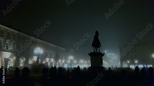 Fotografie, Obraz Silhouette People Surrounding Monument With Illuminated Buildings In Background