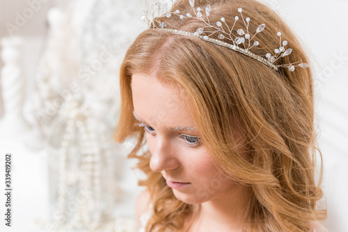 Romantic young bride in elegant hotel room in white lace wedding dress with makeup and wavy blonde hair with pearl jewelry getting ready in bride's morning Canvas Print