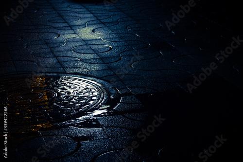 Fototapeta High Angle View Of Manhole On Street At Night obraz