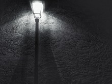 Low Angle View Of Illuminated Lamp Post Against Wall At Night