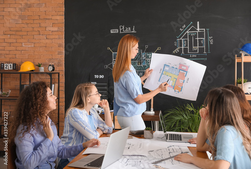 Photo Architect teaching young people in office
