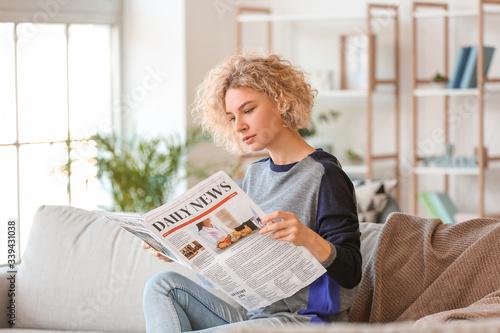 Fotografia, Obraz Beautiful young woman reading newspaper at home