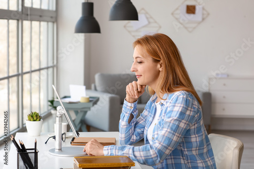 Mature woman using tablet computer for online learning at home Canvas Print