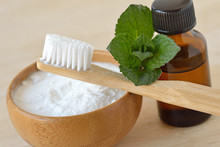 Baking Soda In A Bowl With A Wooden Toothbrush And Peppermint Essential Oil - Homemade Natural Toothpaste