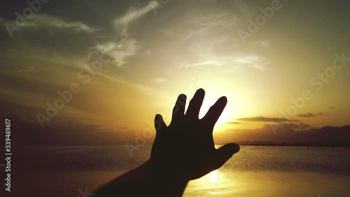 Fotografiet Cropped Hand Gesturing At Sea Shore Against Sky During Sunset