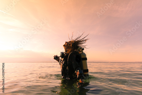 Canvas Print Female Scuba Dive Instructor Wearing a Dry Suit, a Twin Tank and Holding Fins Fl