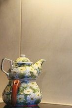 Close-up Of Floral Pattern Teapots On Table Against Wall