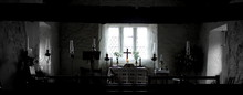 Panoramic View Of Illuminated Candles With Cross On Altar Against Window At Church